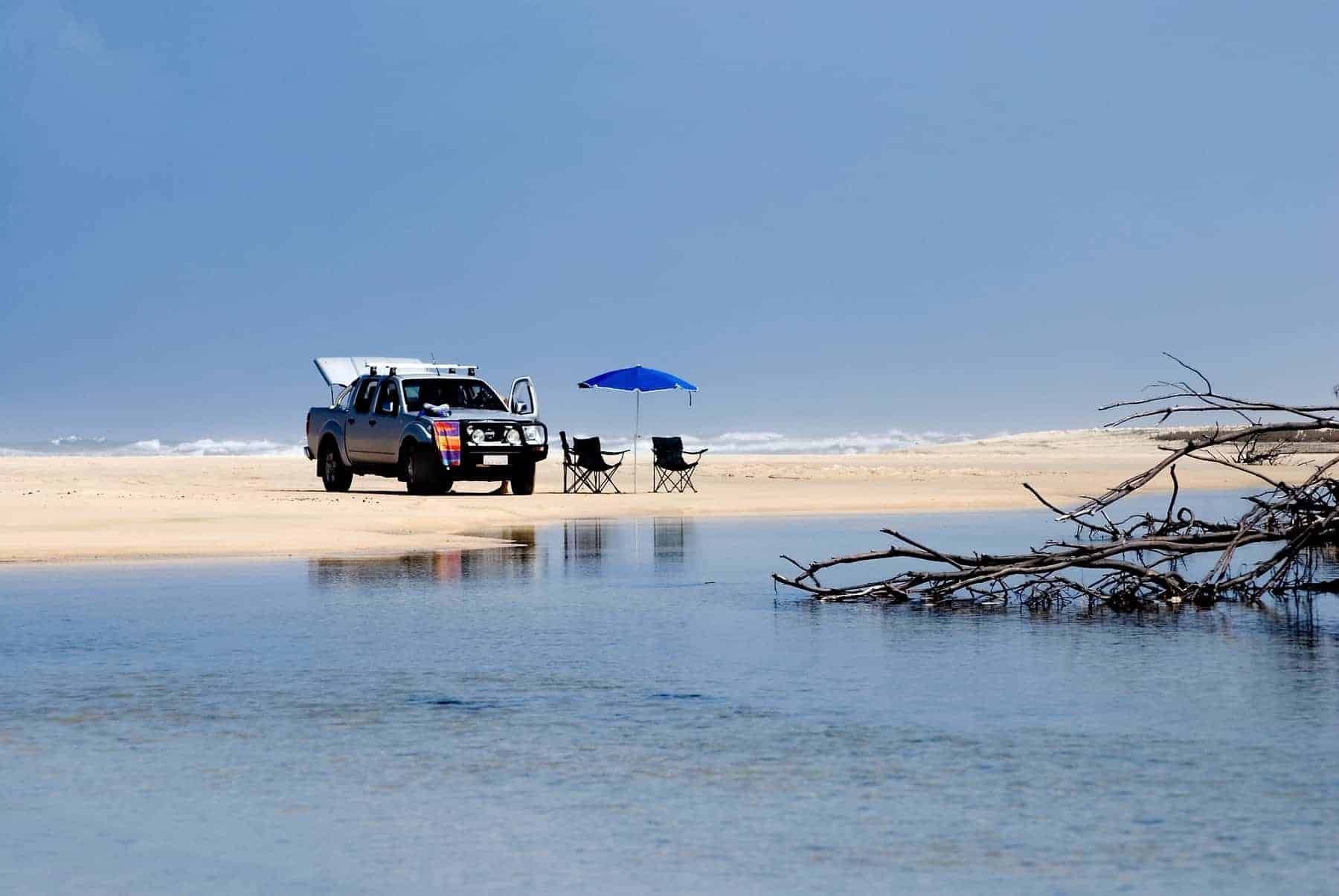 Car with beach chairs and umbrella on the Fraser Island Beach/Queensland/Australia