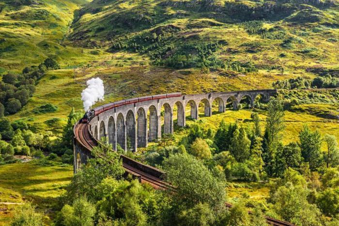 Glenfinnan Railway Viaduct in Scotland with a steam train