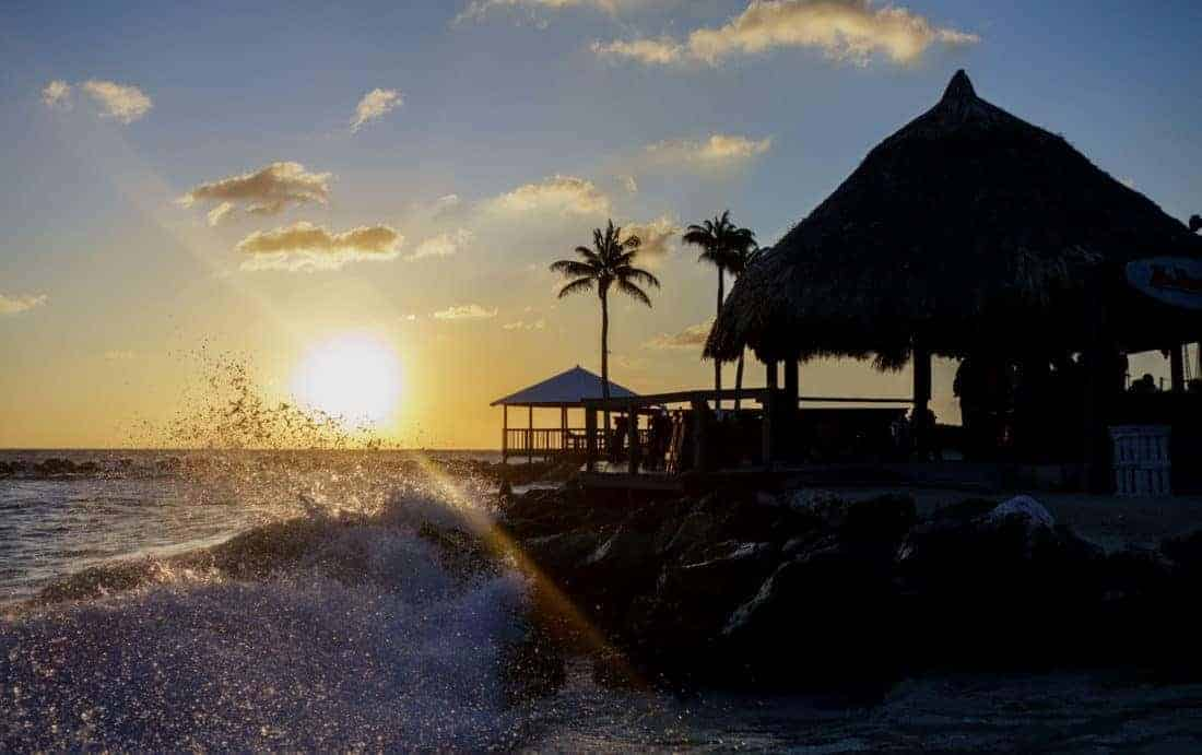 A beautiful sunset on a beach in Curacao with a beach front bar and waves crashing into the shore