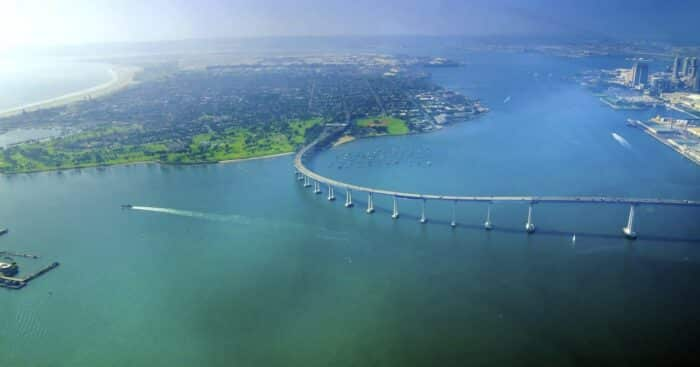 Aerial view of the Coronado island and bridge in the San Diego Bay in Southern California, United States of America. A view of the Skyline of the city and some boats crossing the the sea.