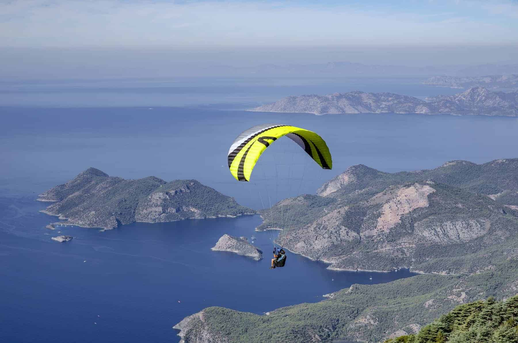 Paraglider fly over the coastline from the top of Babadag