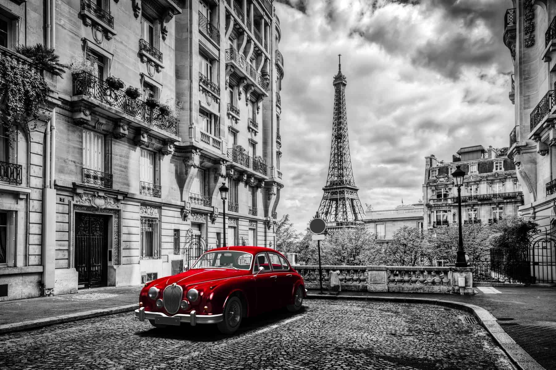Artistic Paris, France. Eiffel Tower seen from the street with red retro limousine car. Black and white unique vintage composition.