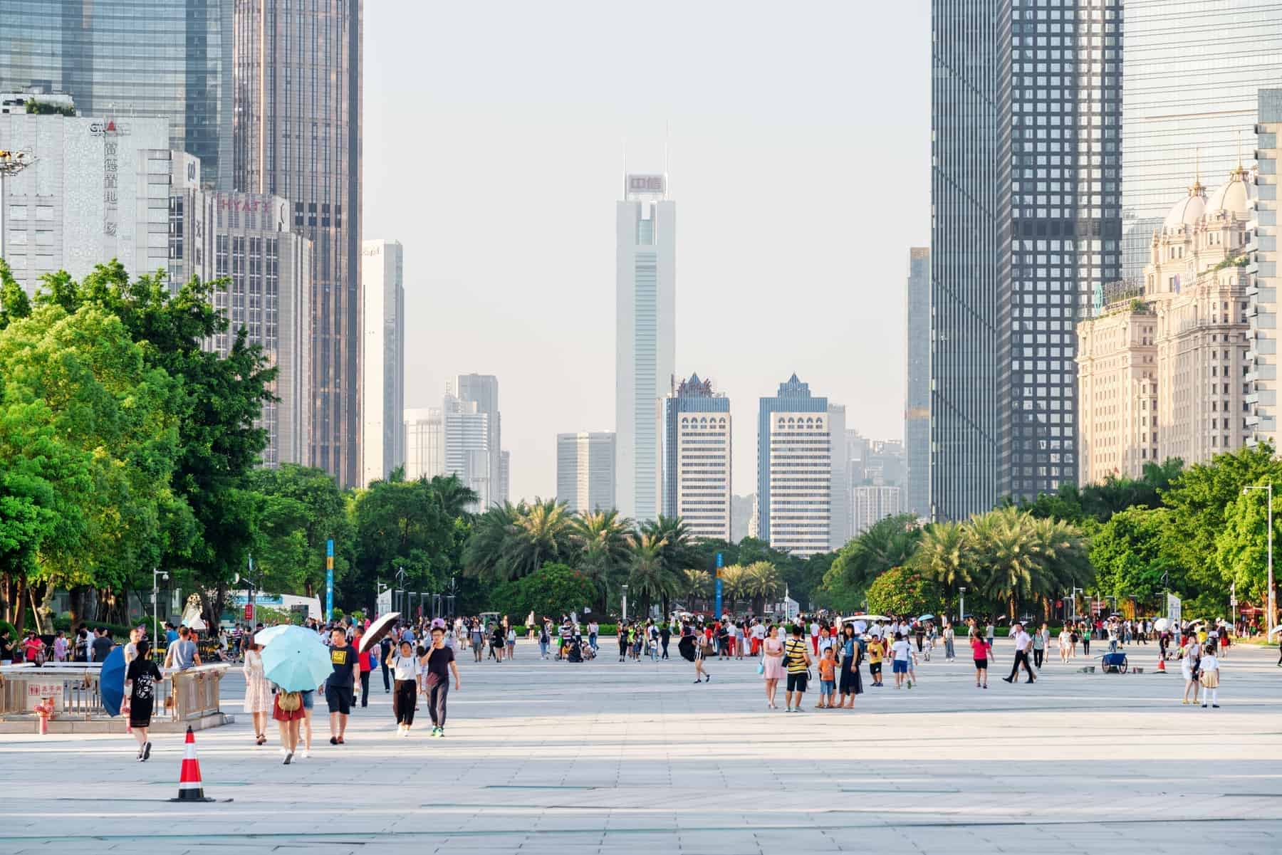 Guangzhou, China - September 16, 2017: Asian tourists walking in a scenic city park among modern buildings in the Tianhe District of the Zhujiang New Town. Guangzhou is a popular tourist destination.