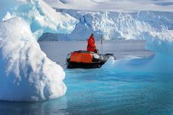 Man sightseeing on small raft amongst beautiful Icebergs at Antarctica.
