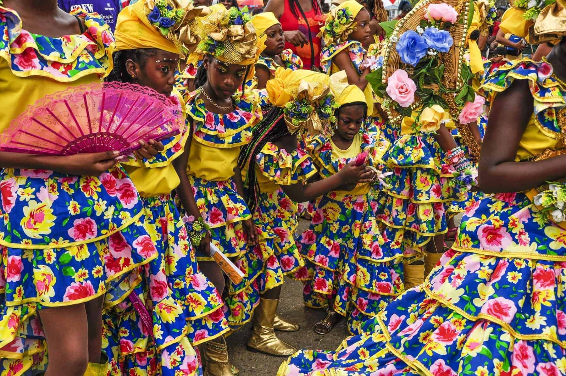 A group of young ladies are dressed in yellow, blue and pink frilly Spanish-styled dresses with head-ties and flowers some carrying fans on Carnival in Trinidad representing the country's Spanish cultural heritage.