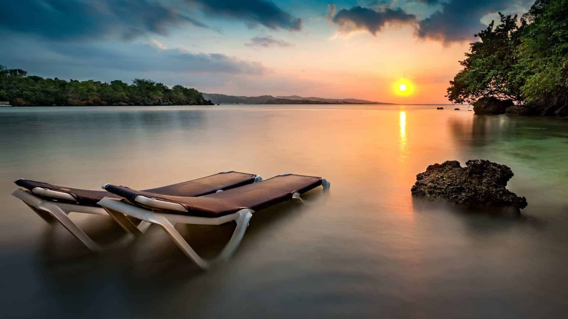 Sunset with beach chairs on a tropical beach in Jamaica.