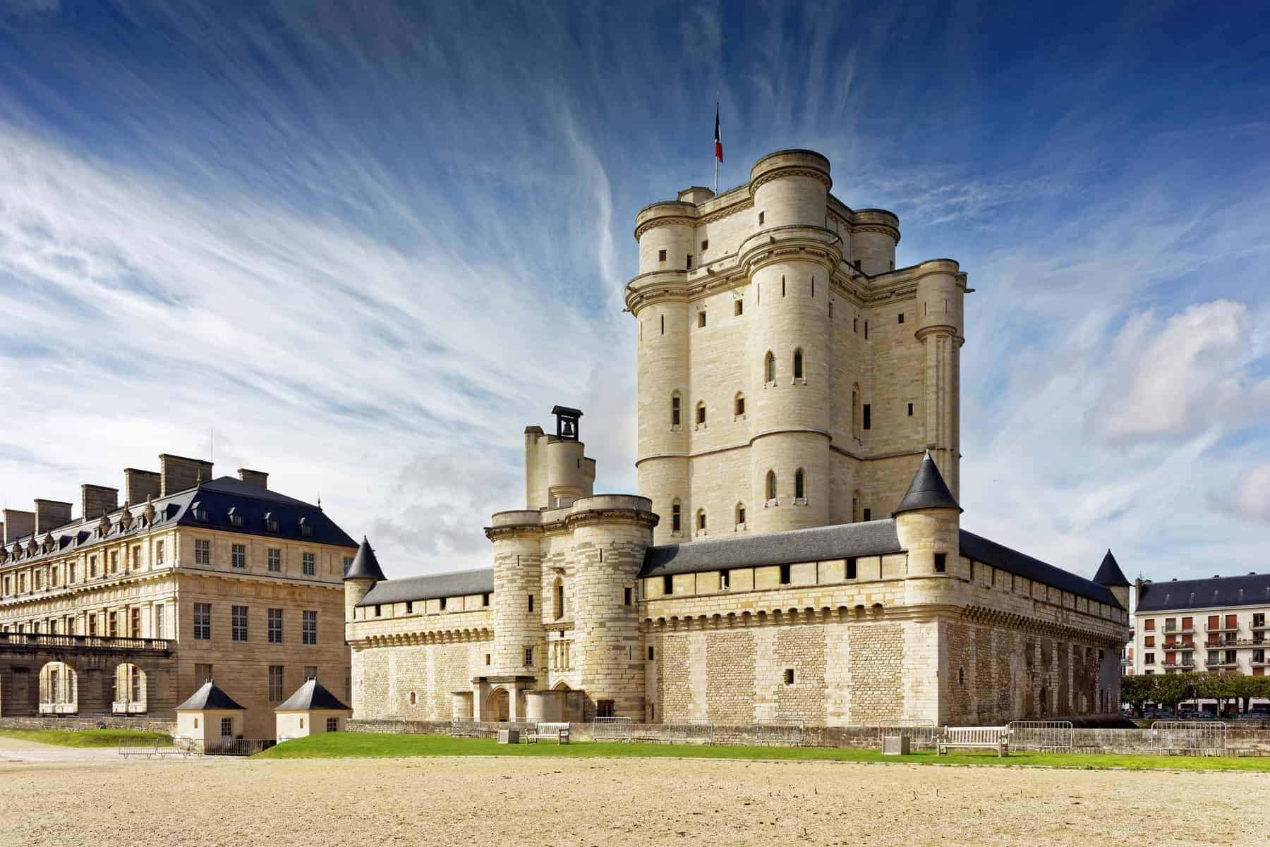 Chateau de Vincennes in Paris. France castle with French national flag under the sunny blue sky.