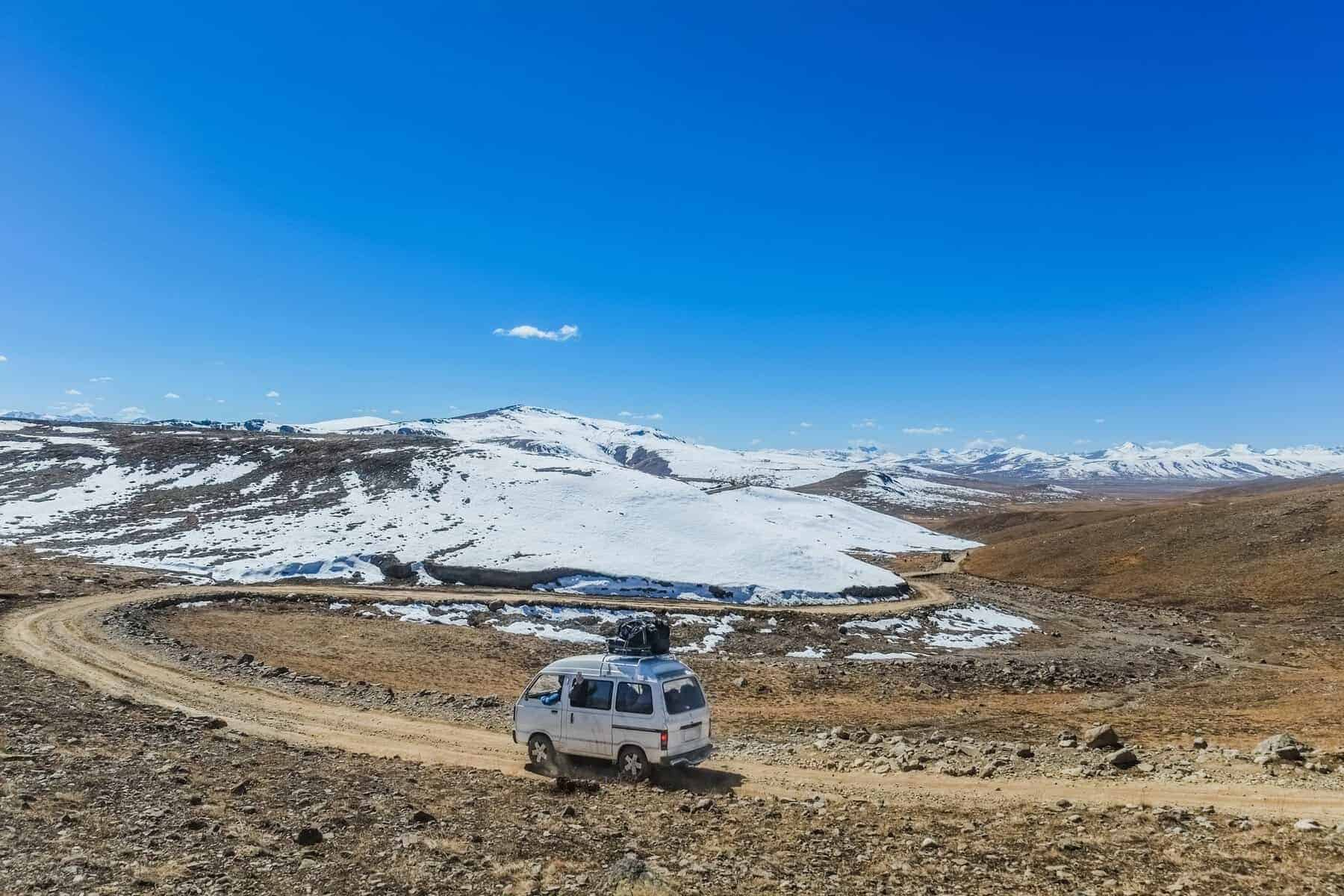 A white van with luggage on the roof running along the unpaved road. Deosai plains, Pakistan.