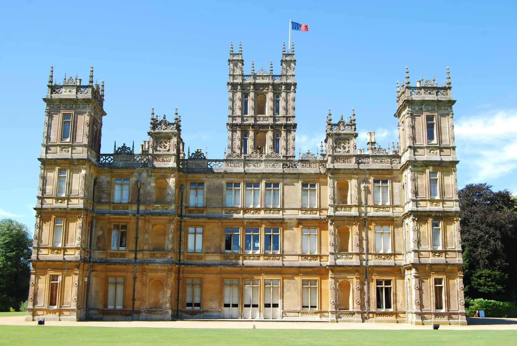 Highclere Castle is a country house in the Jacobean style, with a park designed by Capability Brown. The 5,000-acre estate is in Hampshire, England, United Kingdom, about 5 miles south of Newbury, Berkshire. It is the country seat of the Earl of Carnarvon, a branch of the Anglo-Welsh Herbert family. The architecture is reminiscent of the Houses of Parliament in London. Popular TV show Downton Abbey was largely filmed here and the tour of the castle rooms takes you into many rooms used in the series.