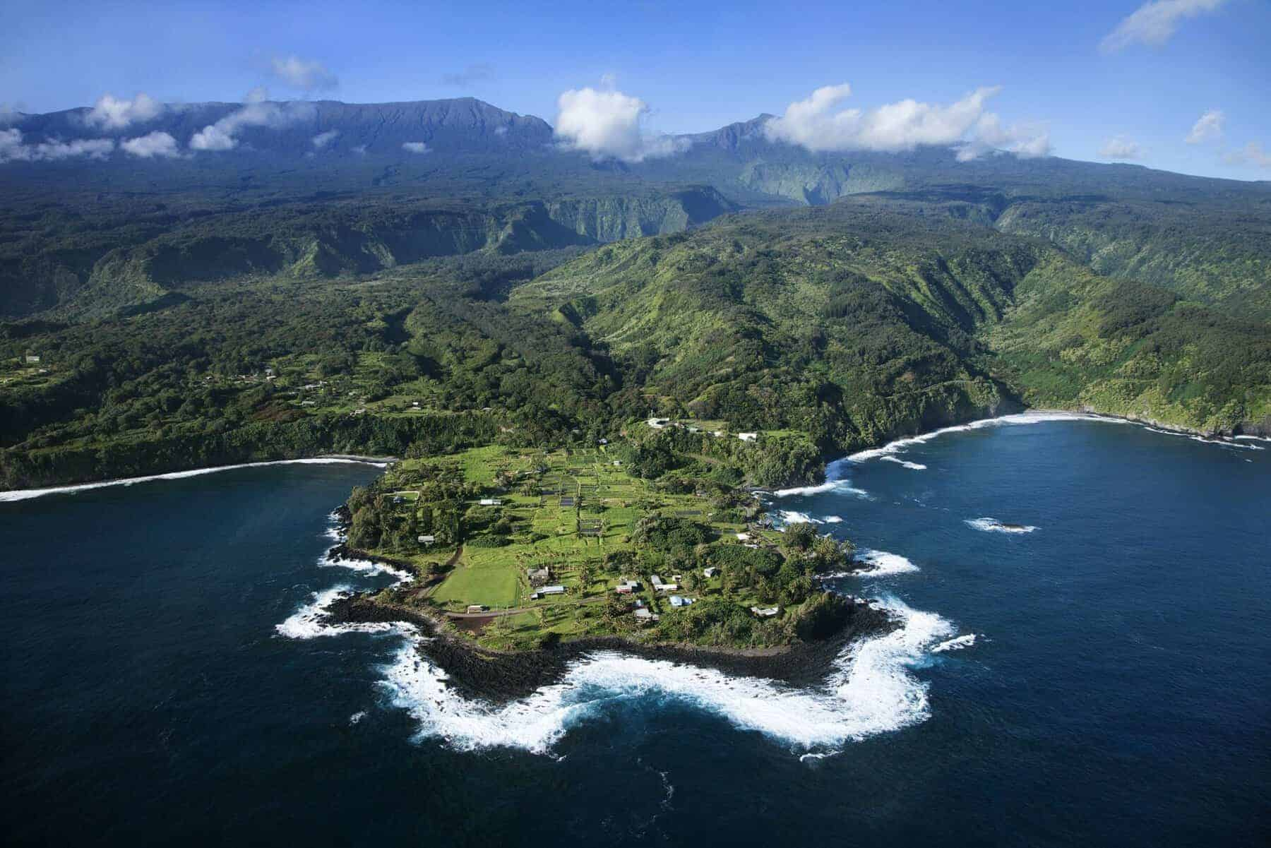 Aerial of rocky coast on Pacific ocean with mountains in background in Maui, Hawaii. Top 15 places to visit in the US