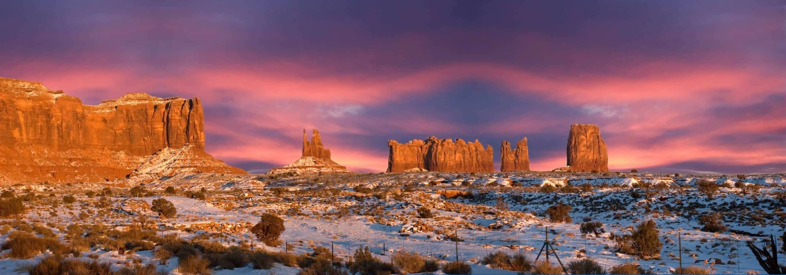 Panoramic sunset scene from the Monument Valley Navajo Indian Reservation Tribal Park in Arizona and Utah. Monoliths rise above the desert and glow as the setting sun shines upon them. Winter snow adds a surreal effect. The area is famous for the old John Ford movies being filmed here, many of them starring John Wayne. Monument Valley is now an international travel destination with people and tourists coming from all over the world just to look at the view.