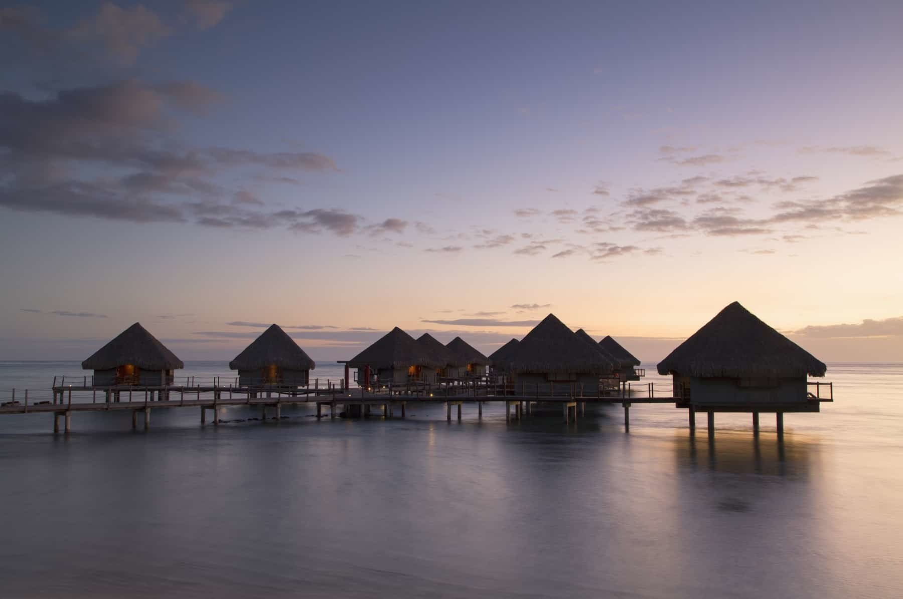 View of overwater bungalows at Le Meridien Tahiti Hotel at sunset, Pape'ete, Tahiti, French Polynesia