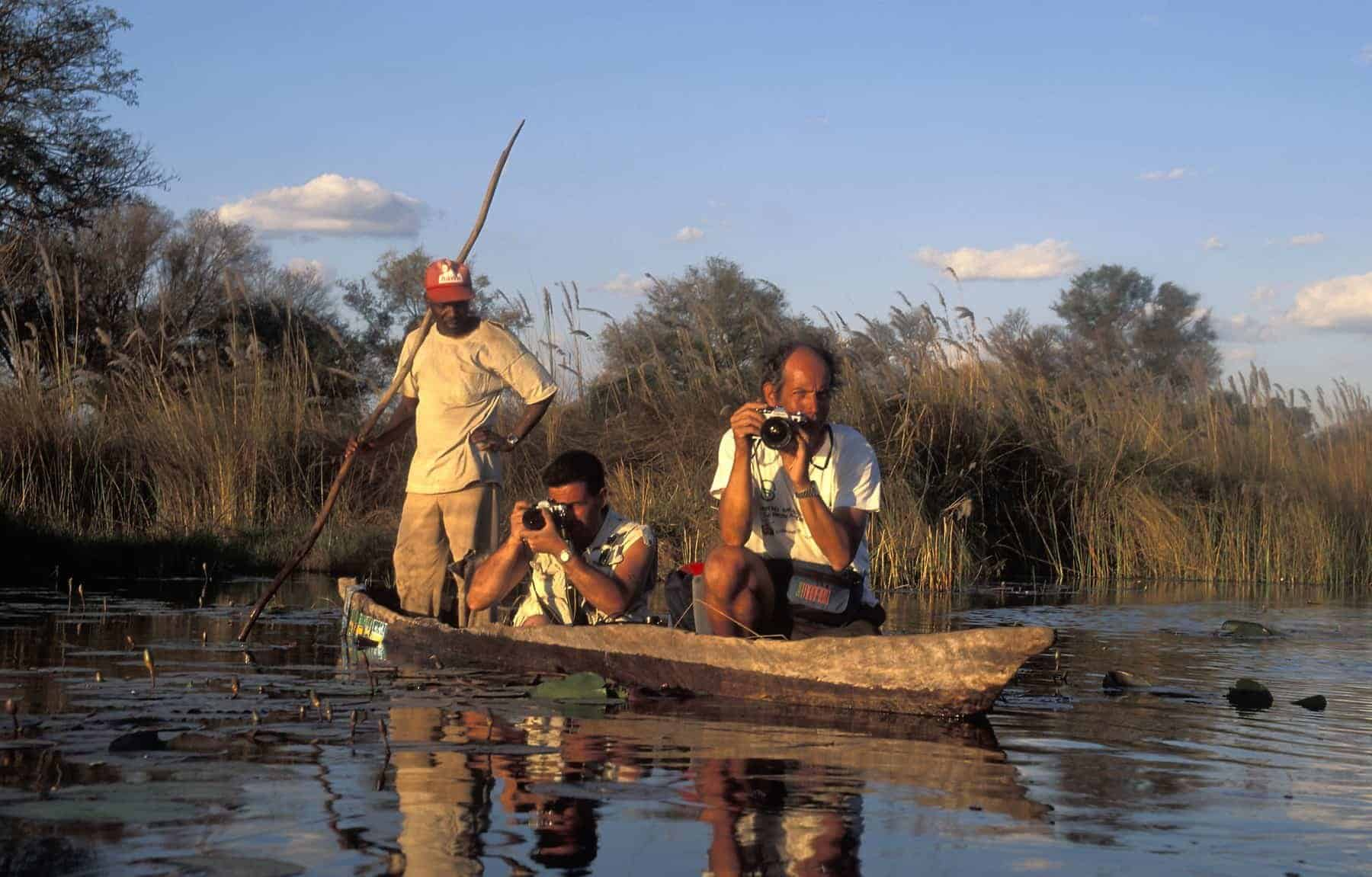 Tourists taking photos from a traditional canoe (mekoro). The mekoro is the typical boat used on the Okavango Delta in Botswana. Hewn from large trunked wild ebony, it is manoeuvred using one wooden pole.