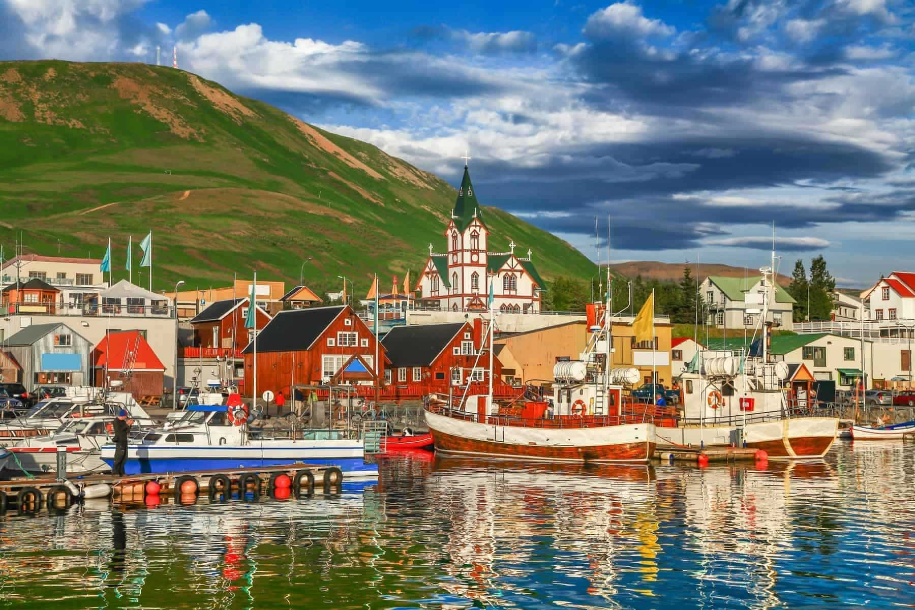 Beautiful view of the historic town of Husavik in golden evening light at sunset, north coast of Iceland