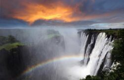 Zambia, Victoria Falls, sunset with rainbow, dramatic sky