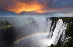 Zambia, Victoria Falls, sunset with rainbow, dramatic sky