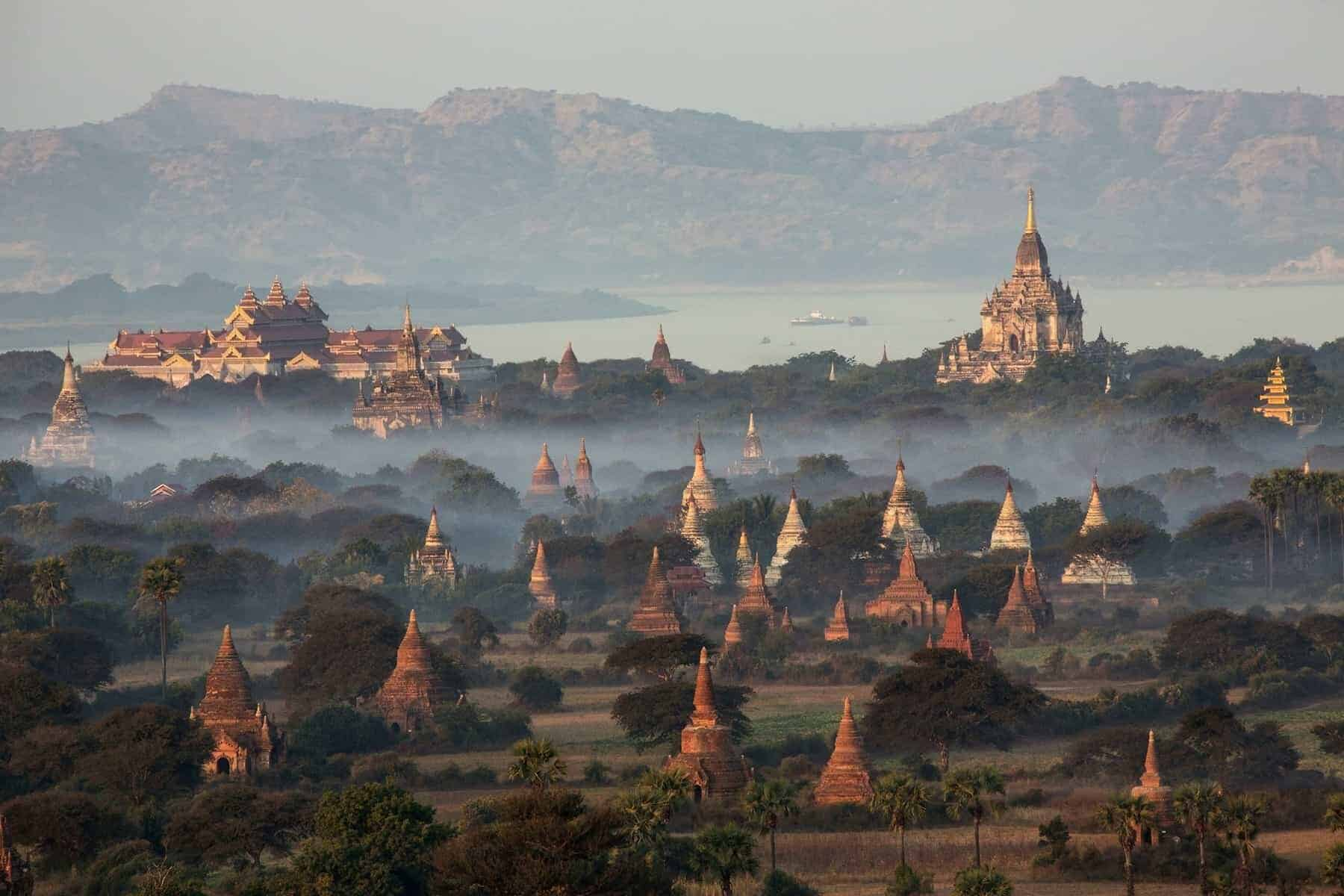 Hot air balloons flying over the temples of the Archaeological Zone in Bagan in the early morning sunlight. In the distance is the Irrawaddy River. Myanmar (Burma).