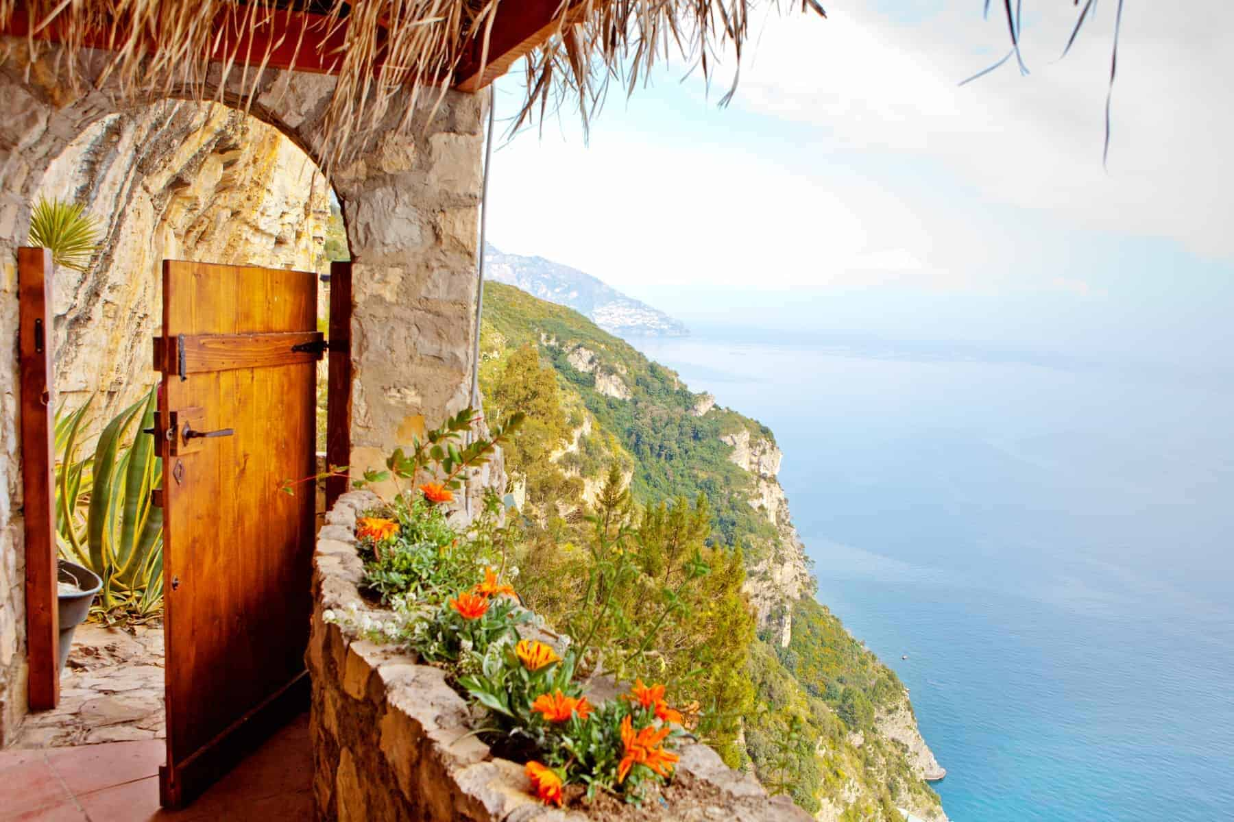 A wooden door leading to a path along a steep cliff on the Mediterranian Sea