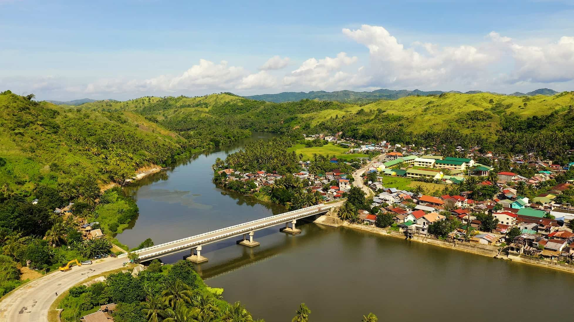 Road bridge on the island of Samar, Philippines.Town on the river bank and road bridge, top view. Bridge over the river, tropical landscape in the afternoon.