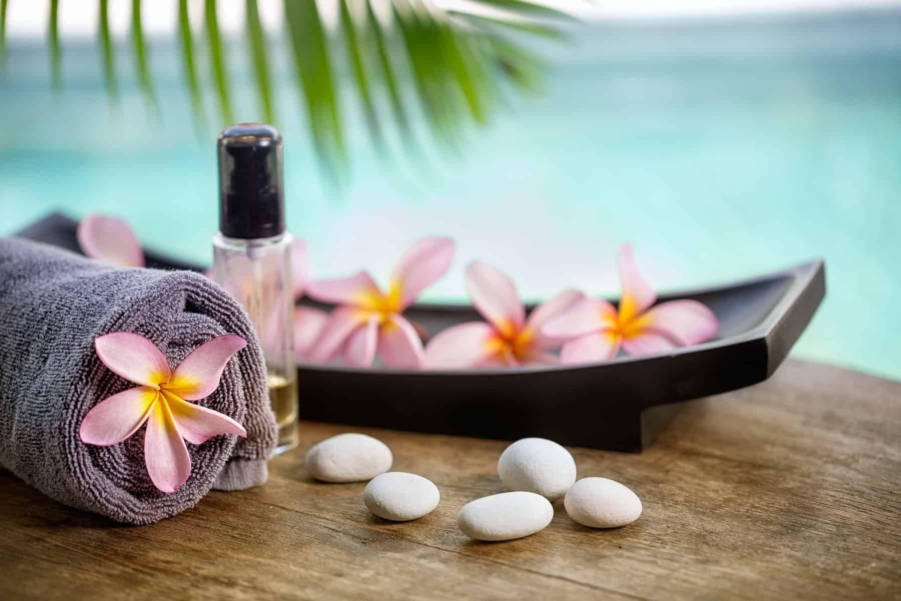 Balinese spa setting, pink frangipani with aromatherapy oil