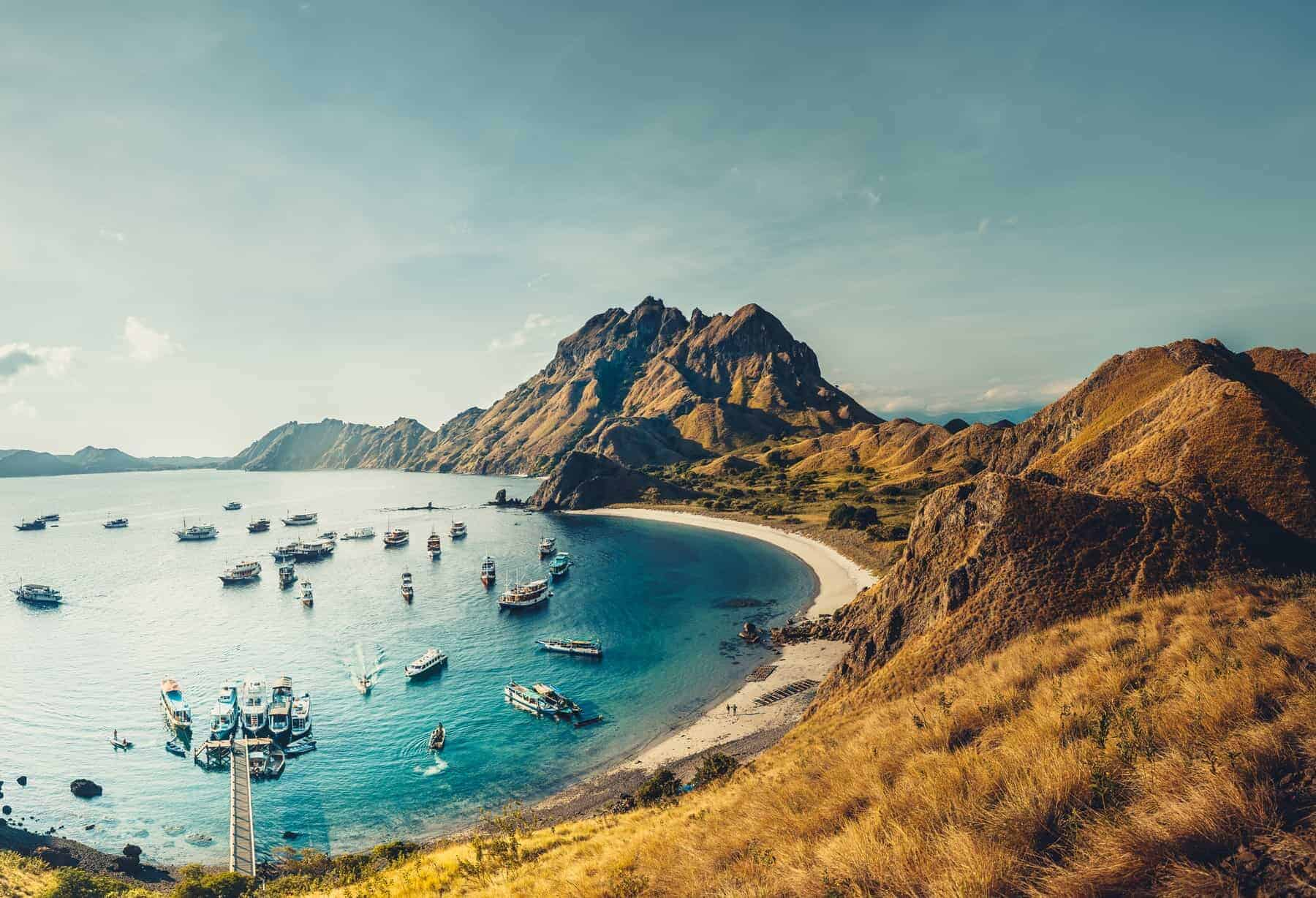 Mountains, ocean bay with boats. Aerial shot. Padar. Wonderful panoramic overview bay with the sand beaches surrounded by the mountains. Landscape of Padar island. Komodo National Park. Indonesia.