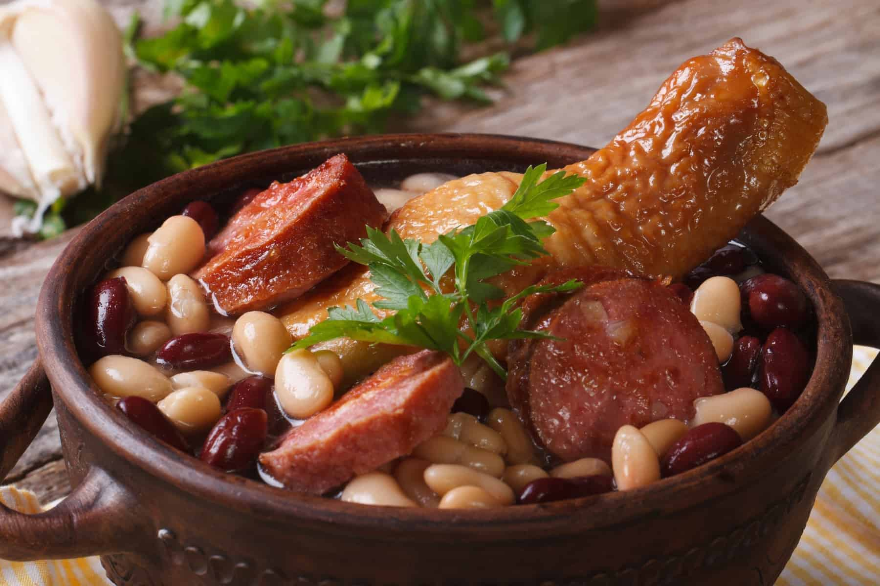 Cassoulet. Beans with chicken legs and grilled sausages close up horizontal