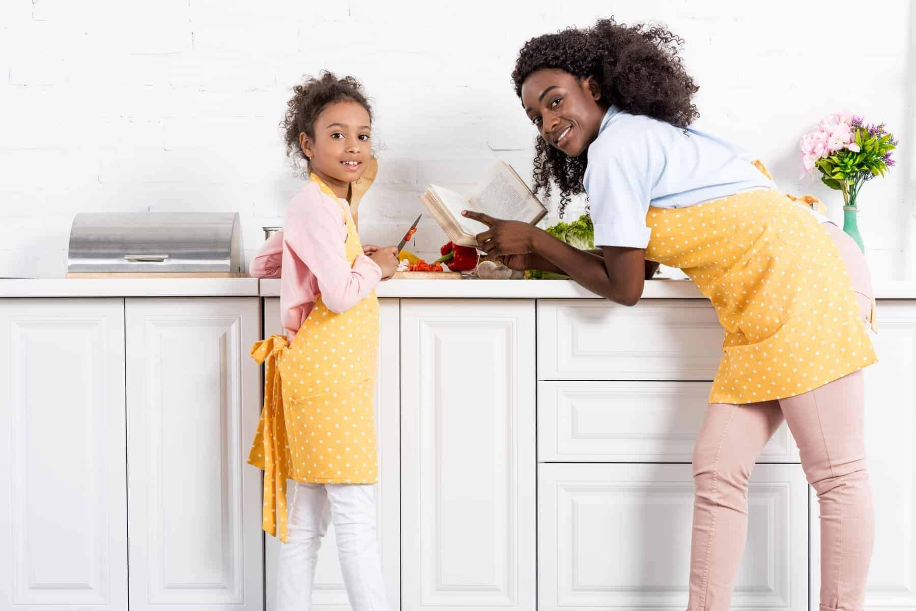 African food. Mother and daughter cooking with cookbook on kitchen