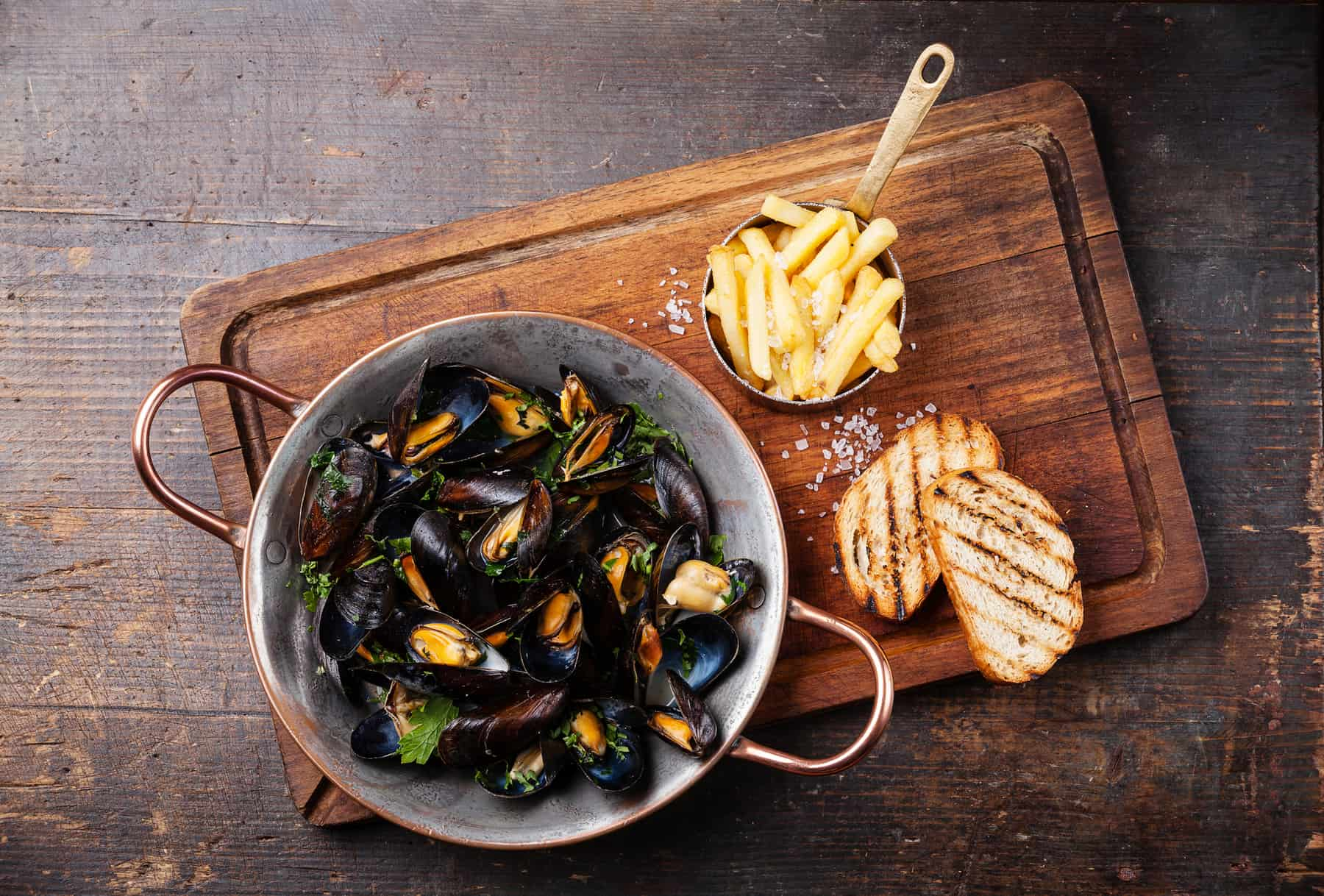 Mussels in a copper cooking dish. The side dish is very often french fries, here seen on a dark wooden background, French cuisine