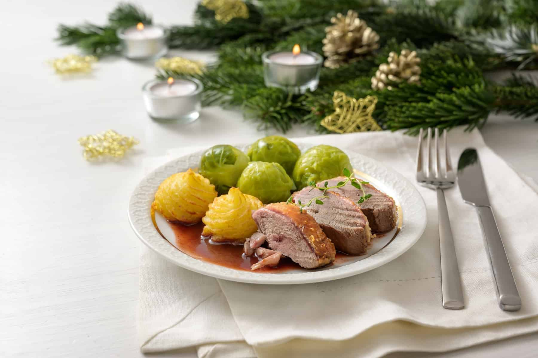 Seared duck breast with brussels sprout, duchess potatoes and sauce as a festive dinner, served on a white wooden table with candles