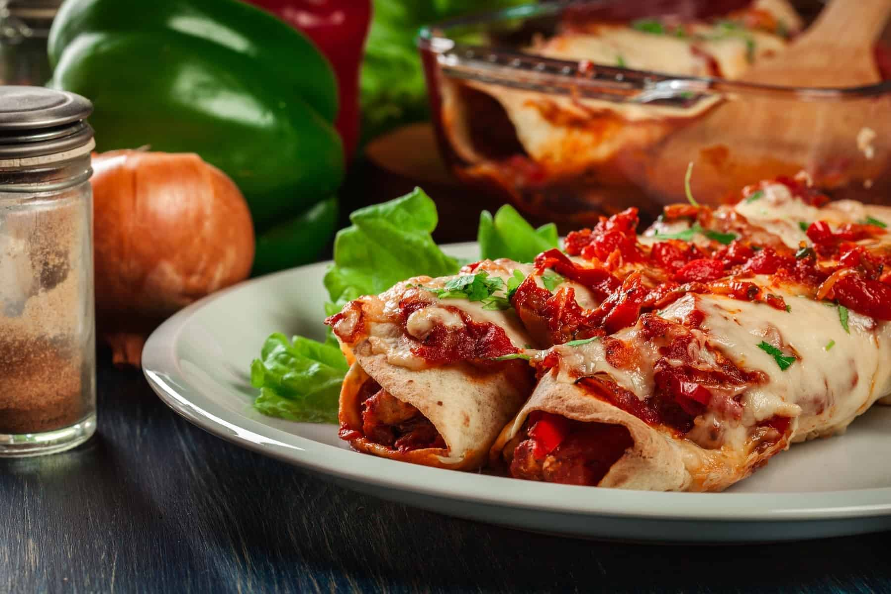 Traditional mexican enchiladas with chicken meat, spicy tomato sauce and cheese on a plate. Mexican cuisine.