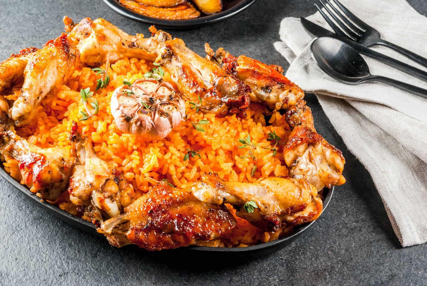 West African national cuisine. Nigeria. Jollof rice with grilled chicken wings and fried bananas plantains.